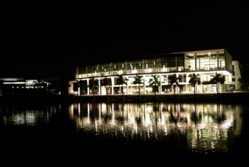 The main campus building lighted up at night and overlooking the lake